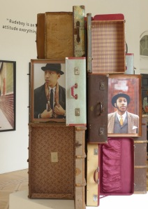 A stack of  suitcases featuring photographic portraiture from the 'Return of the Rudeboy' exhibition.