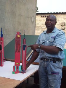 Photograph of the artist Bodys Isek Kingelez next to one of his architectural models.