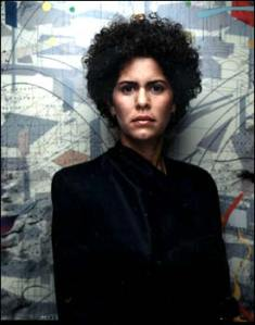 Photograph of the Ethiopian artist Julie Mehretu. in front of one of her abstract paintings. Source: http://faculty.georgetown.edu/irvinem/visualarts/mehretu.html.