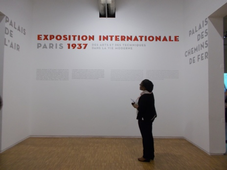 Photograph of Carol Dixon visiting the Pompidou Centre's retrospective of the International Exhibition of Art and Technology in Modern Life (1937), as part of the wider exhibition 'Robert Delaunay: Rythmes Sans Fin' on display in the Level 4 galleries of the Musée National d'Art Moderne (15 October 2014 - 12 January 2015).  Date: 20 November 2014.