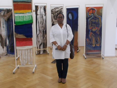 Carol Dixon in front of paravents produced by El Hadji Sy in 2013. These works were designed as double-sided mobile sculptures attached to aluminium frames produced by Mathis Esterhazy.