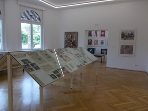 Table vitrine featuring archival documents and news cuttings about El Hadji Sy's political activism. Poster art and film monitors playing footage of performance installations can be seen in the adjoining room.