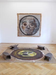 Wall painting: Portrait du President (2012), acrylic and tar on butcher's paper, 190 x 200 cm. Floor painting: Le Puits (2014), acrylic and tar on jute sacking, 245 x 280 cm. El Hadji Sy's artworks are displayed with four stools from Papua New Guinea that are part of the Weltkulturen Museum collection.