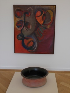 Untitled (1992) oil on canvas by El Hadji Sy, displayed with a Brazilian pot from the Weltkulturen Museum collection.
