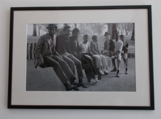 """A framed image of """"Young Men on a Seesaw"""" (1984), by Vanley Burke."""