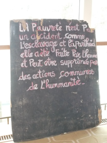 "A placard declaring that ""Poverty is not an accident..."" - which featured as part of Alpha Diagne's installation. The artist set up ""The Blue House"" (2016) as a make-shift art museum in the Calais refugee camp where he used to live"
